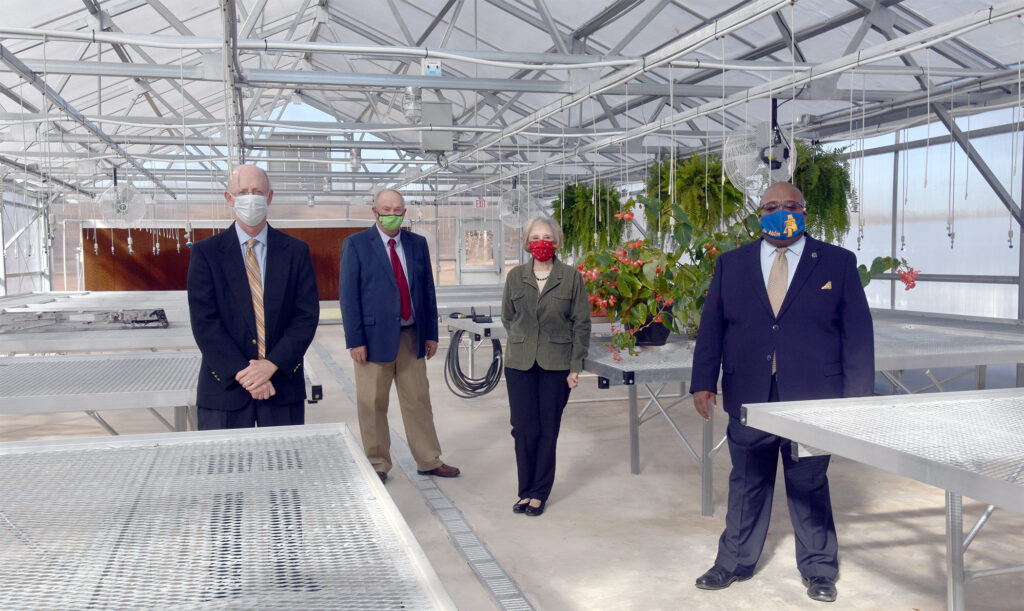 People stand in the greenhouse, part of the Agribusiness Technology program.