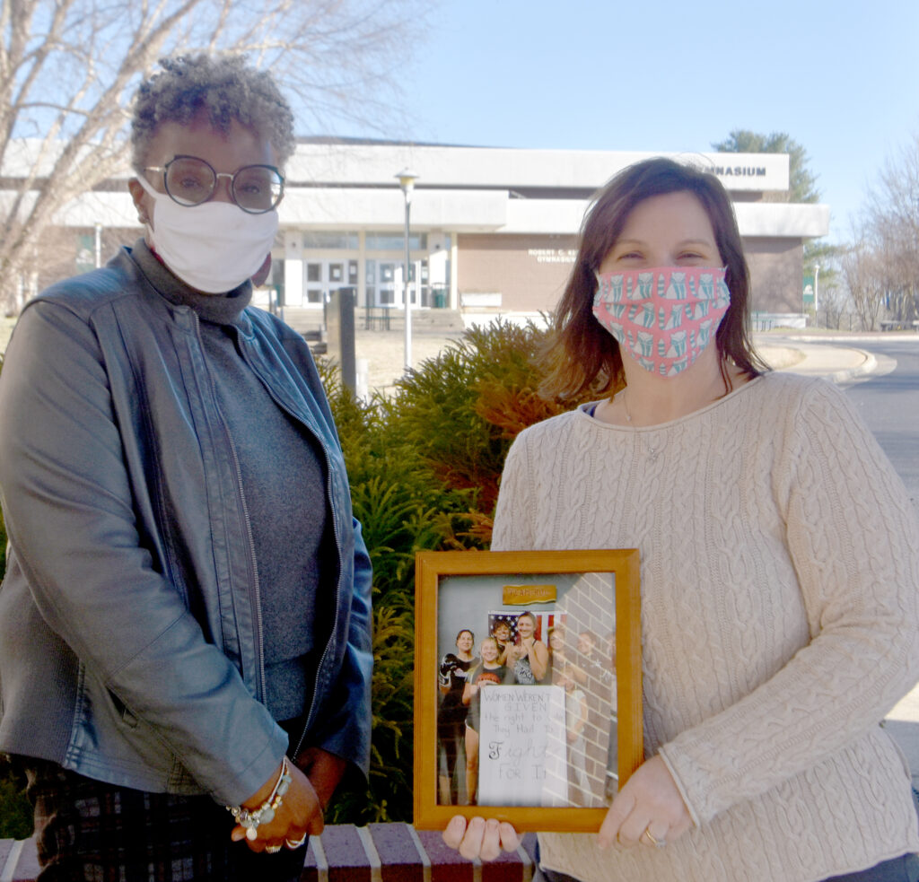 Valencia Abbott presents Tracy Yoder with a framed copy of Yoder's winning photo.