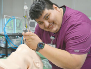 Roberto Reyes puts a tube down a mannequin's throat during Respiratory Therapy class.