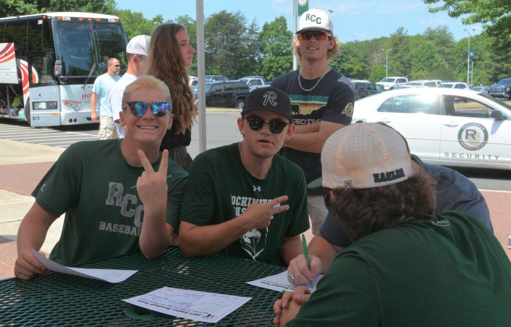 Baseball players sign autographs