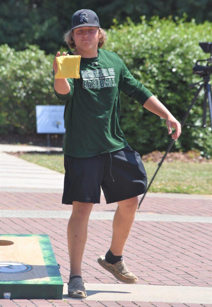 Baseball player tosses cornhole bag