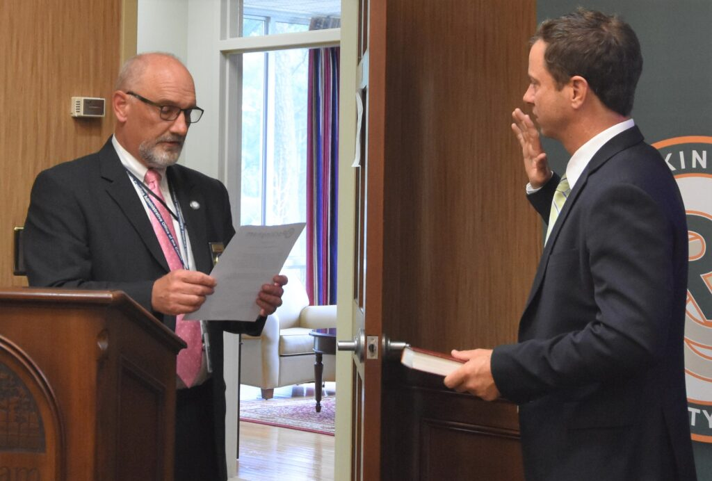 Rockingham County Clerk of Court J. Mark Pegram, at left, administers the oath of office to incoming RCC Board of Trustees member Charles K. Rakestraw on July 20, 2021.