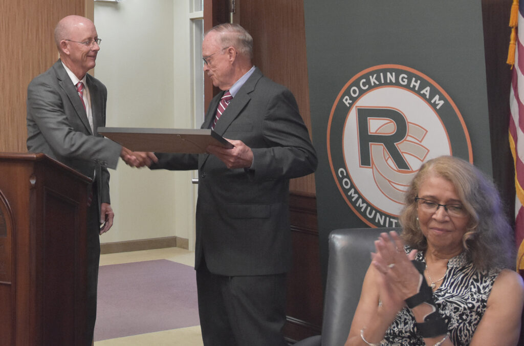 RCC President Dr. Mark Kinlaw, at left, shakes hands with outgoing Board of Trustees member Robert Shelton, as incoming board vice president Randy Judkins applauds.